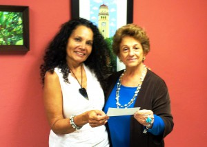 Candida Gonzalez accepting the check for the Joan Fayer award from Interim Director Alma Simounet